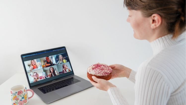 Woman enjoying an afternoon tea while talking to friends on her laptop
