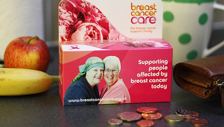 A Breast Cancer Care home donation box and some coins