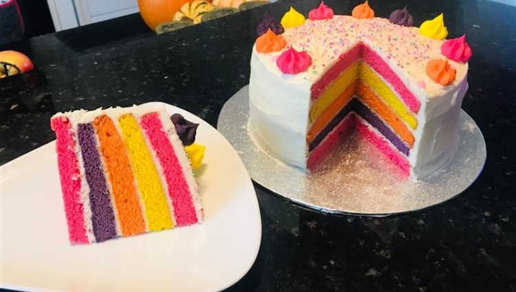 a slice of cake with rainbow layers