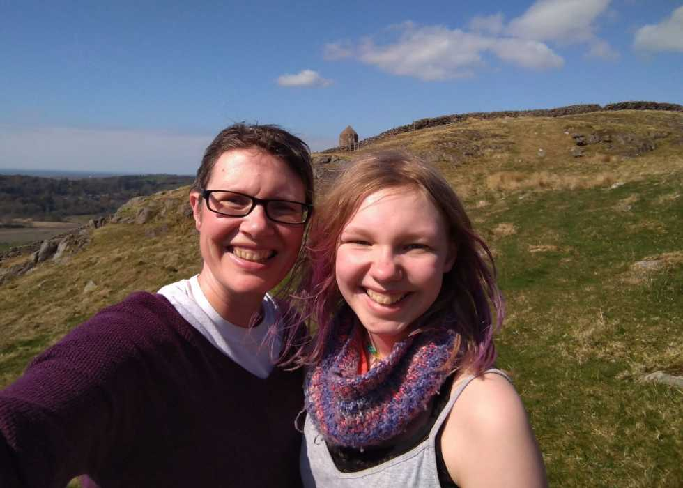 Dawn, a white woman with cropped brown hair, smiles with her daughter, Eve, who has long blonde hair and a colourful scarf. They are enjoying the sunny countryside.