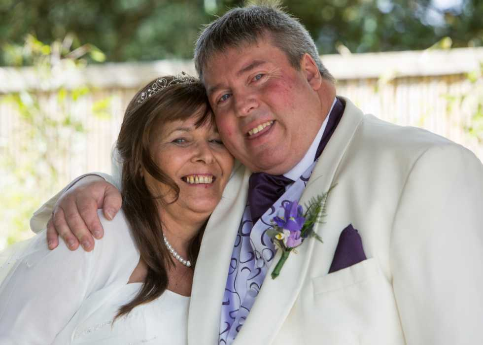 Barry and his wife, Iris, on their wedding day. Iris has long brown hair and a broad smile. Barry has cropped grey hair and is smiling widely in his white suit.