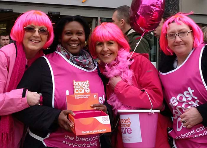 A group of Breast Cancer Care fundraisers holding buckets