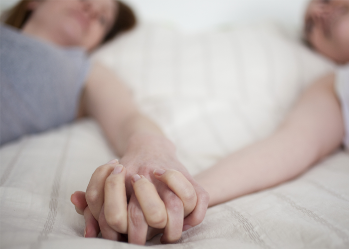 A couple holding hands in bed