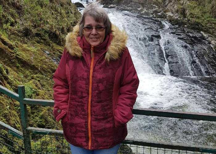 Iris, who has cropped grey hair, is wrapped up warm in a red coat. She is standing in front of a rushing river.