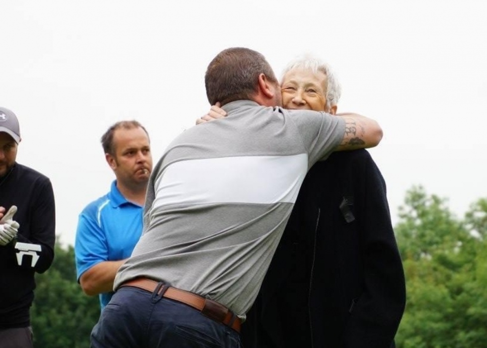 Rhys hugs his mum, Jen, on the golf course