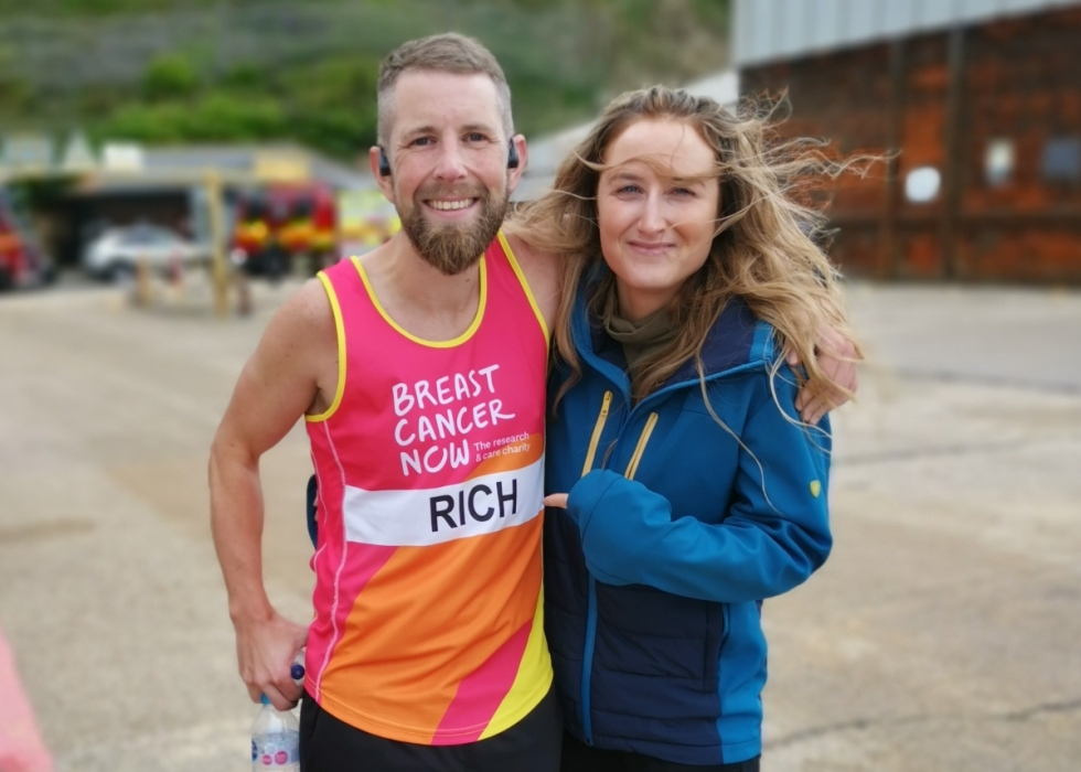 Rich, a white man with sandy brown hair and a beard, smiling in his Breast Cancer Now running gear