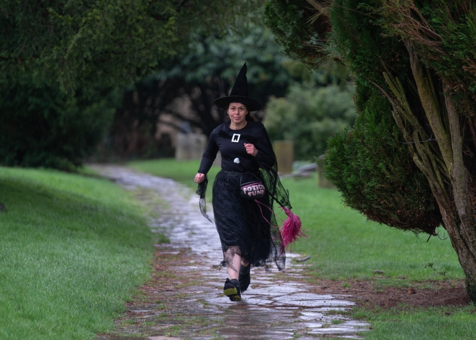 Judy, a white woman with dark hair, running outside in her trademark witch outfit