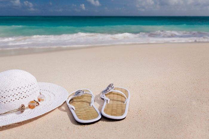 A pair of sandals, a beach hat, and a book on a white sand beach with a blue sea in the background