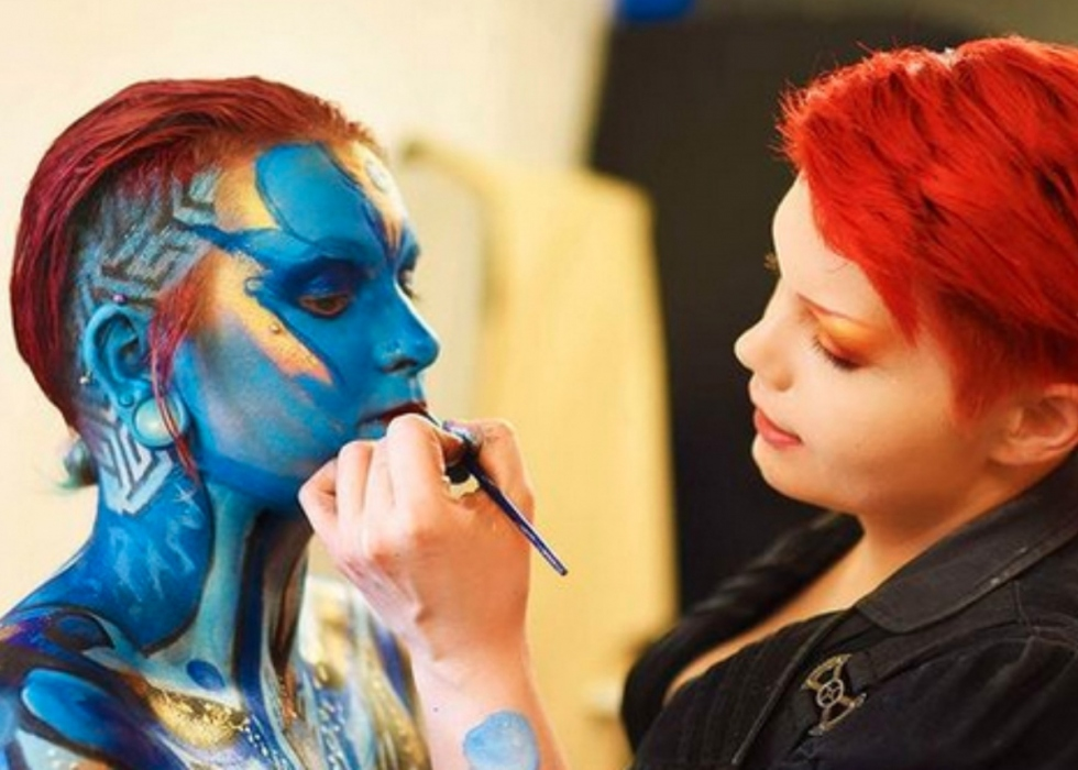 Victoria, a young white person with red hair, paints a model's face