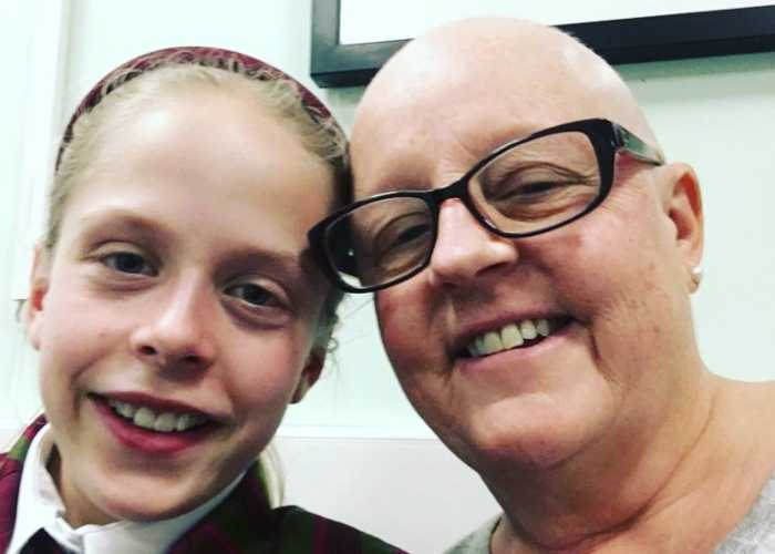 Vicks, a white woman with a shaved head and glasses, smiles with her 11-year-old daughter, Poppy