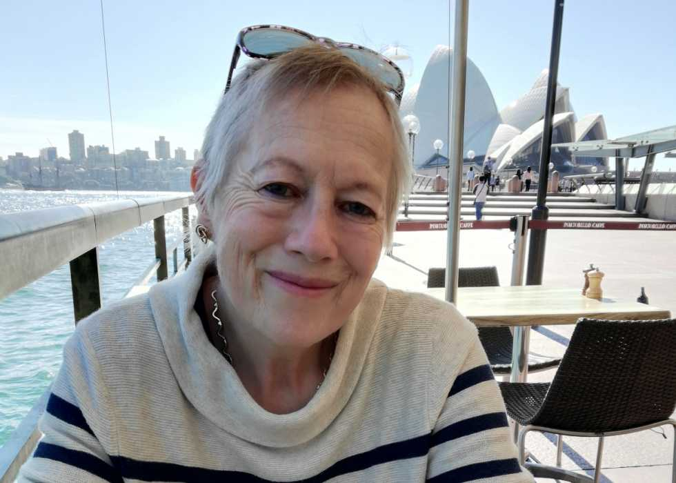 Fran, a white woman with short grey hair, smiles while wearing a white jumper. In the background, the Sydney opera house is visible.