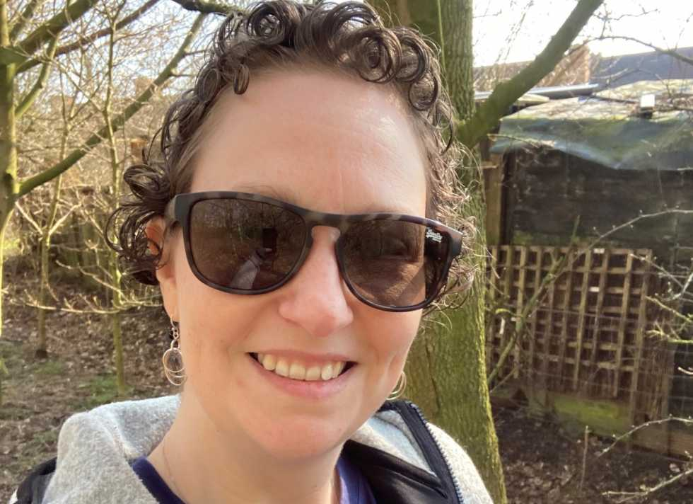 Gail, a white woman with curly brown hair, wears sunglasses while out for a walk