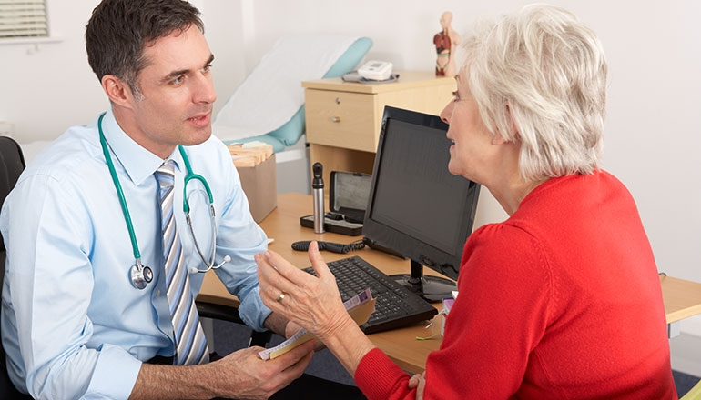 A male doctor speaks with an older female patient at an appointment