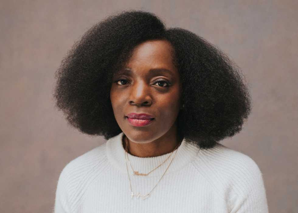 Jennifer, a Black woman with natural hair, sits for the camera while wearing a white jumper