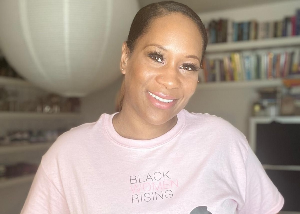 Leanne, a young Black woman, smiles for the camera in her 'Black Women Rising' t-shirt