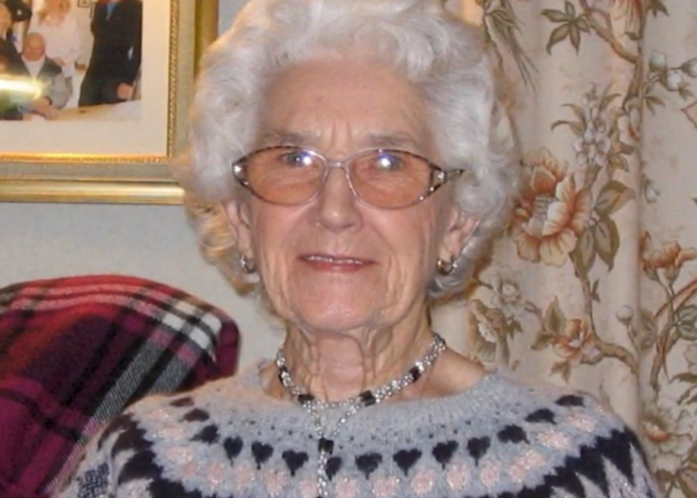 Margaret, an elderly lady with white hair and glasses, smiles at the camera