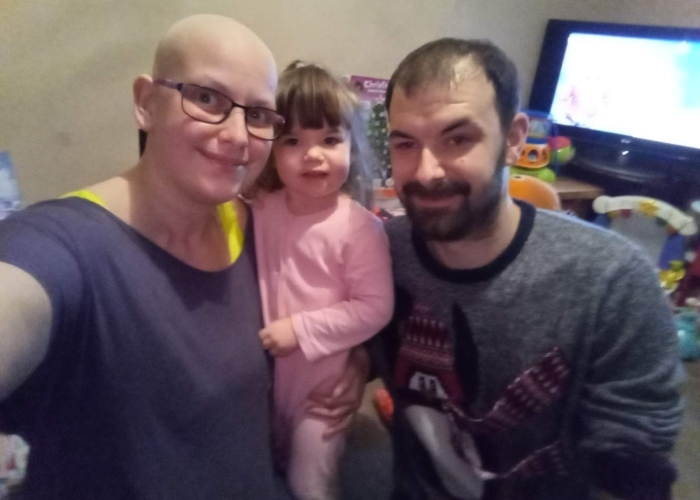 maxine with her head shaved after chemo, at home with her husband and daughter