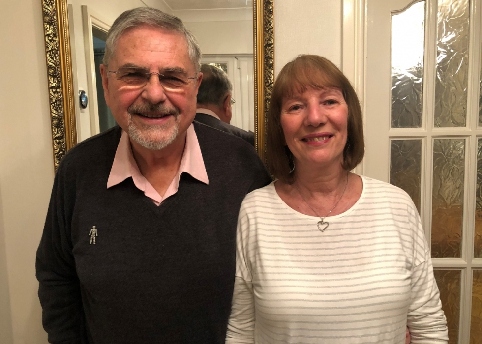 Richard and Karen, an older couple, stand next to each other smiling