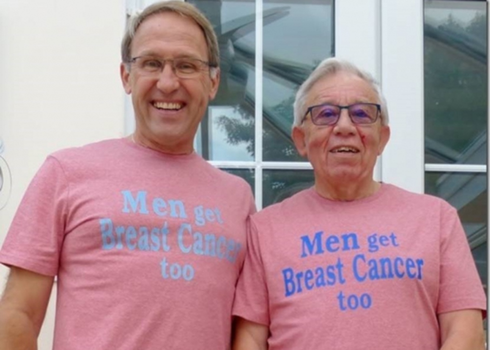 two men , roger and his husband, wearing t shirts that say 'men can get breast cancer too'