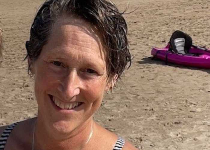 Sarah, a white woman with short, brown hair, smiles while out at the beach.