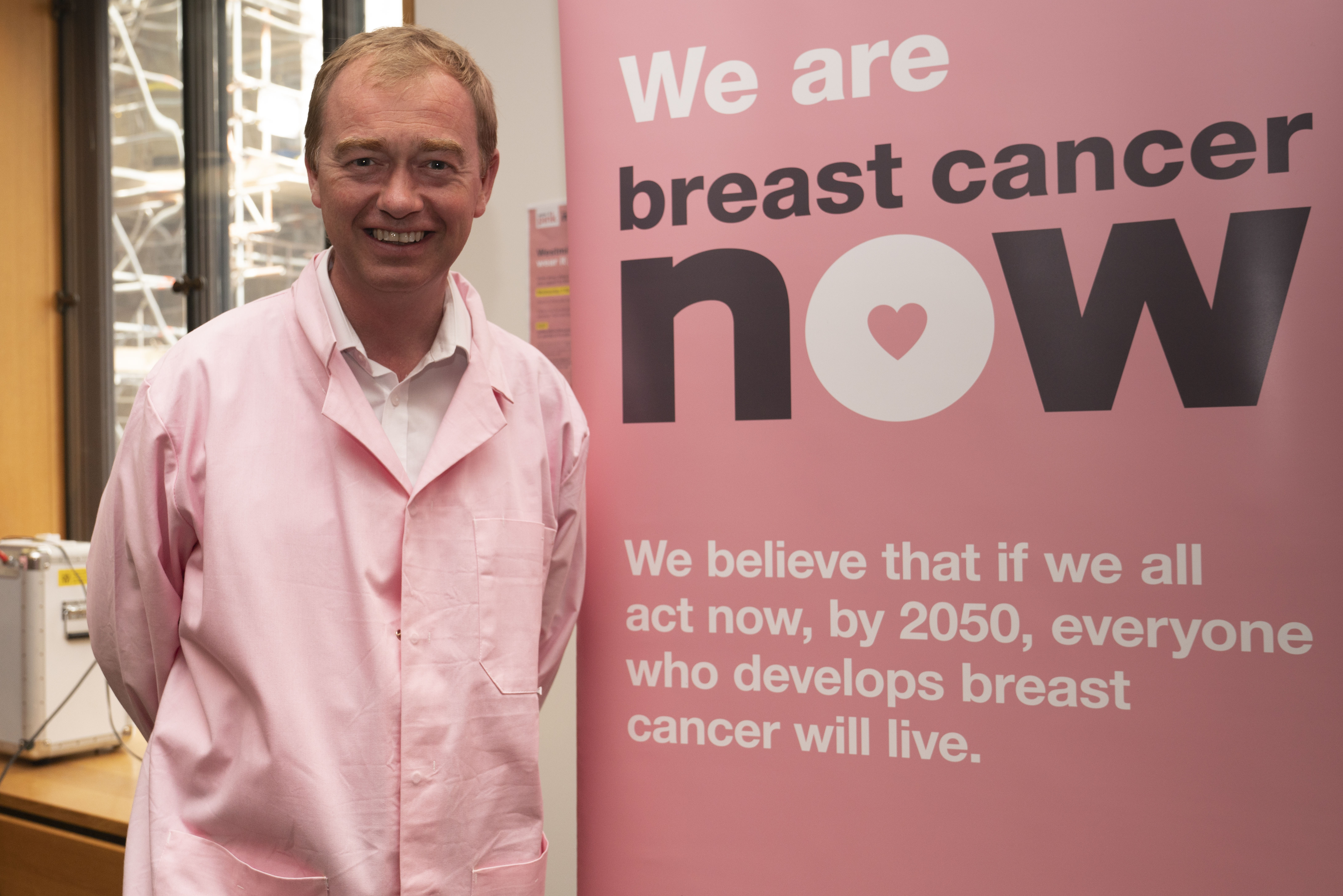 Tim Farron infront of Breast Cancer Now banner