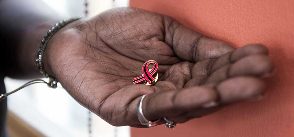 A hand holding a pink and black striped secondary breast cancer pin