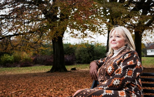 woman sitting on a park bench in autumn