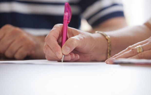 A hand holding a pen over a piece of paper