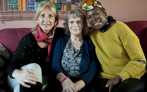 Cynthia, Caroline and Debs sitting on a sofa wearing a Unity Band for World Cancer Day