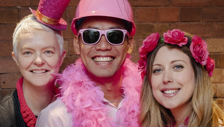 Two women and a man dressed in pink accessories