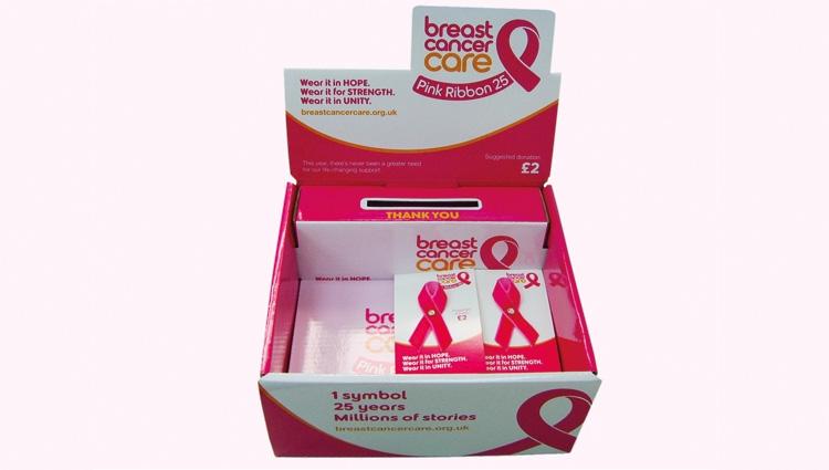 A box of pink ribbon pin badges