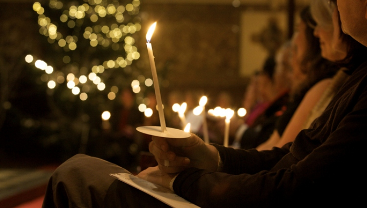 Person holding candle in carol service