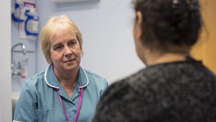 Nurse talking to woman in breast clinic