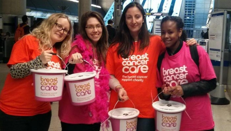 Group of people holding buckets in a station with Breast Cancer Care t-shirts