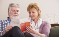 A man and woman looking at a Breast Cancer Care publications