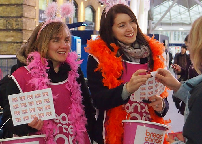 Two women holding Breast Cancer Care collection buckets