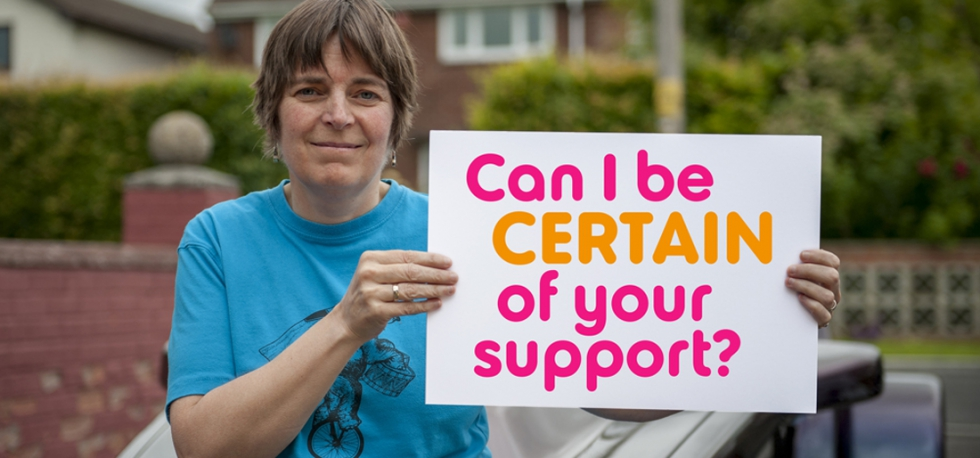 Dawn standing with 'can I be certain of your support' sign