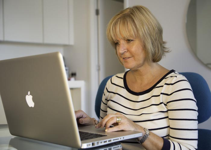 A woman smiling while typing on a computer