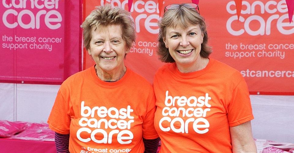 Two Pink Ribbonwalk volunteers in orange t-shirts