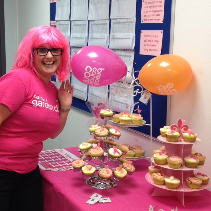 A women in pink stood next to some cupcakes