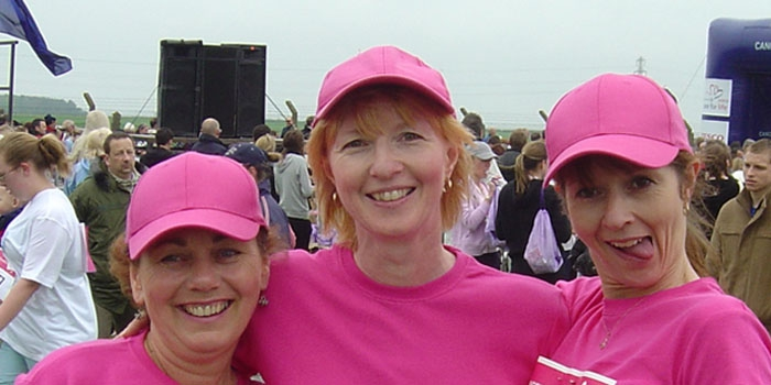 Stephanie stands in the middle of two friends, dressed in pink at a fundraising event