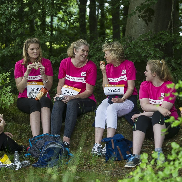 Women in pink t-shirts and walking boots having a picnic