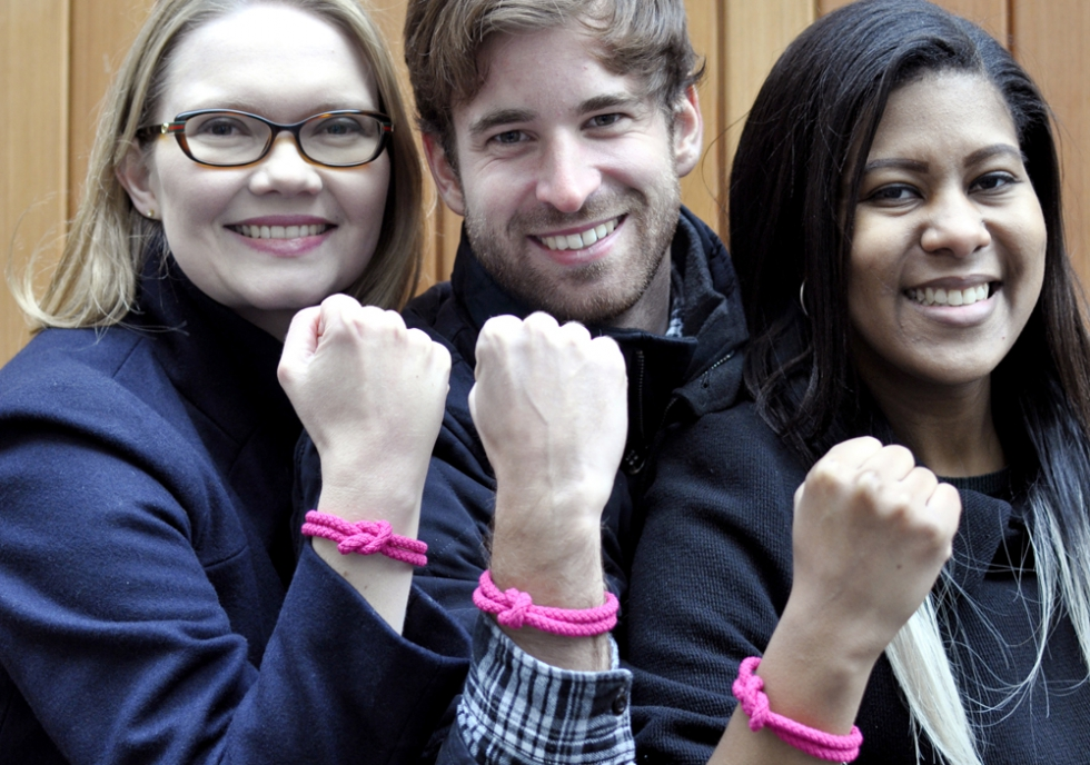 4 people wearing world cancer day bands and smiling