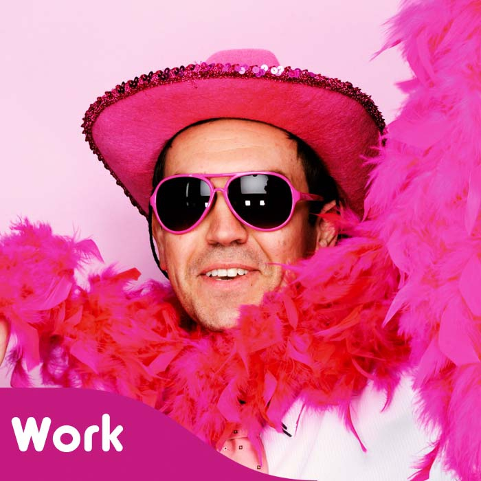 A Big Pink fundraiser in a cowboy hat and feather boa