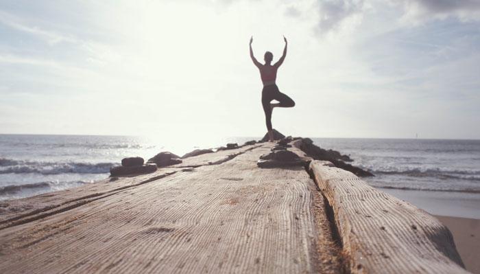 A woman doing yoga against an ocean back drop
