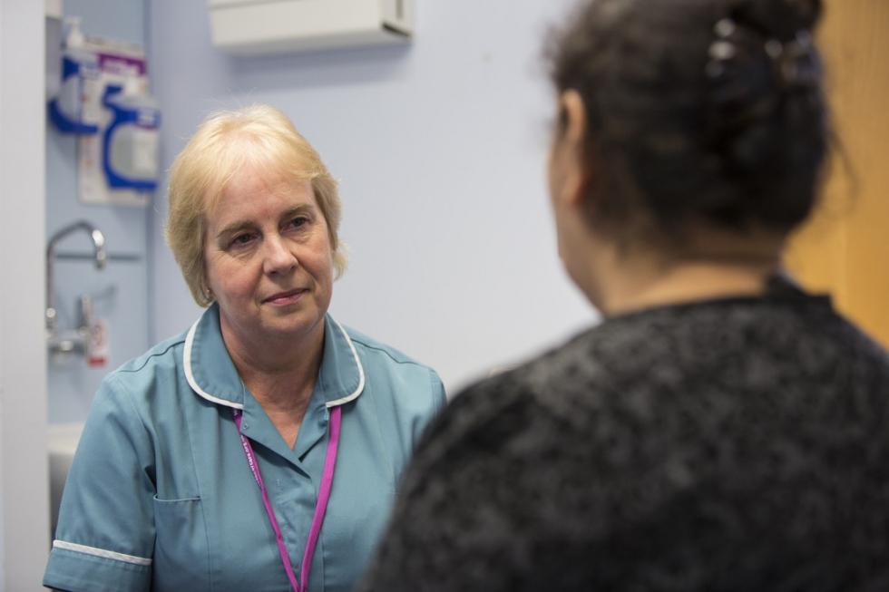 Nurse talking to woman in breast clinic