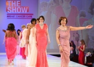 Women who have had breast cancer walking down a catwalk in evening gowns