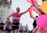 A Breast Cancer Care supporter runs and waves to the crowd