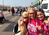 Three Breast Cancer Care cyclists celebrate completing the London to Brighton bike ride by holding their medals on the seafront.