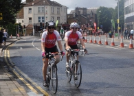 Two cyclists riding in support of Breast Cancer Care